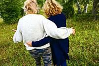 Slite, Gotland, Sweden Two women walking arm in arm.