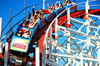 Thrill seekers scream and raises their hands as they descend on the historic wooden Giant Dipper rollercoaster in Santa Cruz, California.