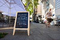 Humorous sign outside a cafe in Belgrade, Serbia with passerby.