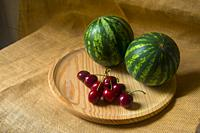 Two watermelons and cherries on wooden dish. Still life.