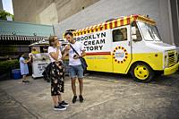 Visitors to the Dumbo neighborhood of Brooklyn in New York enjoy free mini-cones from the Brooklyn Ice Cream Factory on Sunday, August 11, 2019. Forme...