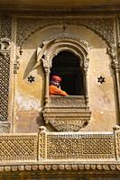 JAISALMER, RAJASTHAN, INDIA, November 2018, Tourist in traditional Rajasthani turban inside carved window of Kothari's Patwon ki Haveli.