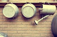 Metal Watering Cans by Brick Wall in garden wood shelf.