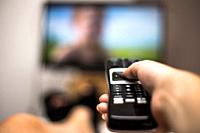 Hand Holding Use Remote Control and Watching TV in House on a colorful flatscreen modern design.