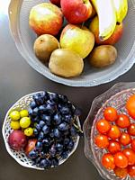 Healthy and fresh various fruit in a bowl on the table top view, grapes, apples, bananas healthy lifestyle colorful.