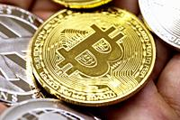 Golden Bitcoin in a man hand, Digitall symbol of a new virtual currency with black and white background.