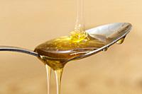 Shiny golden honey dripping off of a silver spoon with a wooden brown background sweet.
