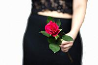 Woman with a red rose in her hand close-up, romantic valentines concept beauty.