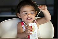Two year old girl drinking fruit juice