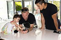 Little girl and two adult men look at a mobile phone.