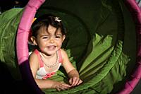 two year old girl in toy tunnel