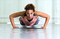 Young woman making push-ups.