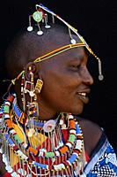 Profile portrait of Masai woman adorned with traditional bead work and colour glass perls around her neck. Masai Mara National Reserve, Kenya.