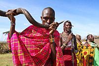 A Masai man blows an Ikudu horn and play music for tradionnal dancing. Masai Mara National Reserve, Kenya.