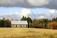 Farm building of stone surrouded by harvested field and trees in autumn colours on a beautiful day of October. Salo, Finland.