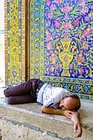 Man sleeping on the door. Agha Bozorg mosque. Kashan, Iran. Asia.