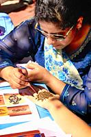 Asian woman painting a henna design on a young woman's hand.