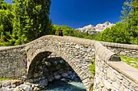 Young hiker crossing the old bridge of Bolática River, Panticosa, Tena Valley, Pyrenees (Huesca province, Aragón, Spain)
