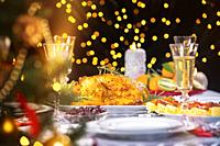 Christmas dinner. Closeup photo of tasty baked chicken against glowing Christmas lights and burning candles. Holiday decorated table, Christmas tree, ...