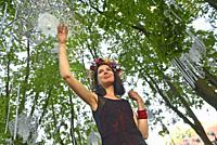 young woman under movable geometrical constructions suspended in trees, Saint John Feast, Klaipeda, port city on the Baltic Sea, Lithuania, Europe.