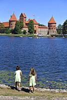 little girls by the Lake Galve with the Castle of Trakai in the background, Lithuania, Europe.