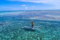 Aerial drone bird's eye view photo of young woman practising paddle board or sup in tropical Caribbean sapphire crystal clear calm waters.
