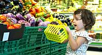 Child shopping eggplants in supermarket. Concept for buying fruits and vegetables in hypermarket. Little girl hold shopping basket.
