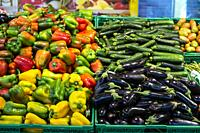 Vegetables in crates in supermarket. Arranged eggplants, peppers and zucchini.
