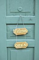 welcome and open signs on green wooden door.