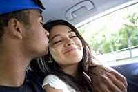 Young couple sitting together in the back seat of car.