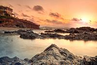 Sunrise at the beach in Marbella with rocks and house.