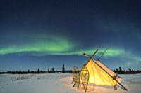 Trappers tent with snowshoes and nightsky with Aurora borealis, Northern lights, Wapusk National Park, Manitoba, Canada.
