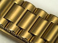 Close up of textures on bracelet of gold plated watch.
