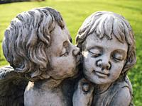 Close up of cupid faces of garden sculpture.