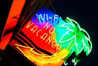A colorful neon sign flashes no vacancy.