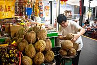 Singapore, Republic of Singapore, Asia - A man weighs and piles up fresh durians at a stall in the Chinatown Market.