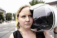 Woman holding motorcycle helmet with a shattered visor, Munich, Germany.