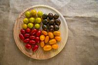 Assorted cherry tomatoes on wooden dish. View from above.