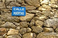 Stone wall and Calle Huertas sign. Avila, Spain.