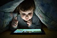 Little girl watching her tablet in the bed. Illuminated child face from device screen. Child dressed with pajamas under the covers hold a tablet. Nigh...