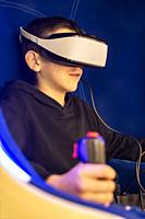 Child playing game with VR glasses. Blue illuminated cabin with joysticks. Special effects. Technology, entertainment and gaming concept with virtual ...