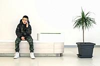 Teenager talking on smartphone in modern commercial center. Bench and flower in a pot. Modern building interior. Technology and communication concept ...