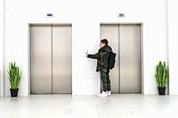 Boy with casual clothes and white sneakers call the elevator. White contemporary building interior. Flowers in pots and white wall. Metallic elevator ...