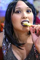 A 41 year old mixed-race asian woman putting food in her mouth, looking at the camera.
