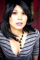 A 41 year old mixed-race asian woman looking at the camera.