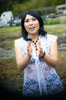 A 41 year old mixed-race asian woman looking at the camera and clapping her hands.