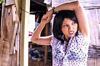 A 41 year old mixed-race asian woman, posing with arms over her head and making a face looking away from the camera.