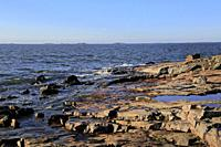 Seaside rocks with view to the blue sea on Kustaanmiekka, the southernmost island of the sea fortress Suomenlinna, Helsinki, Finland. October 2019.