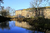 Small pond with reflections of the blue sky and fortifications in Piper's Park, Suomenlinna, UNESCO World Heritage site in Helsinki, Finland. Oct 2019...