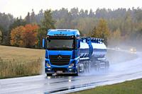 Blue Mercedes-Benz Actros tank truck of Kuljetusliike Markus Hanninen Oy delivers load along wet road on a rainy day. Salo, Finland. October 4, 2019.